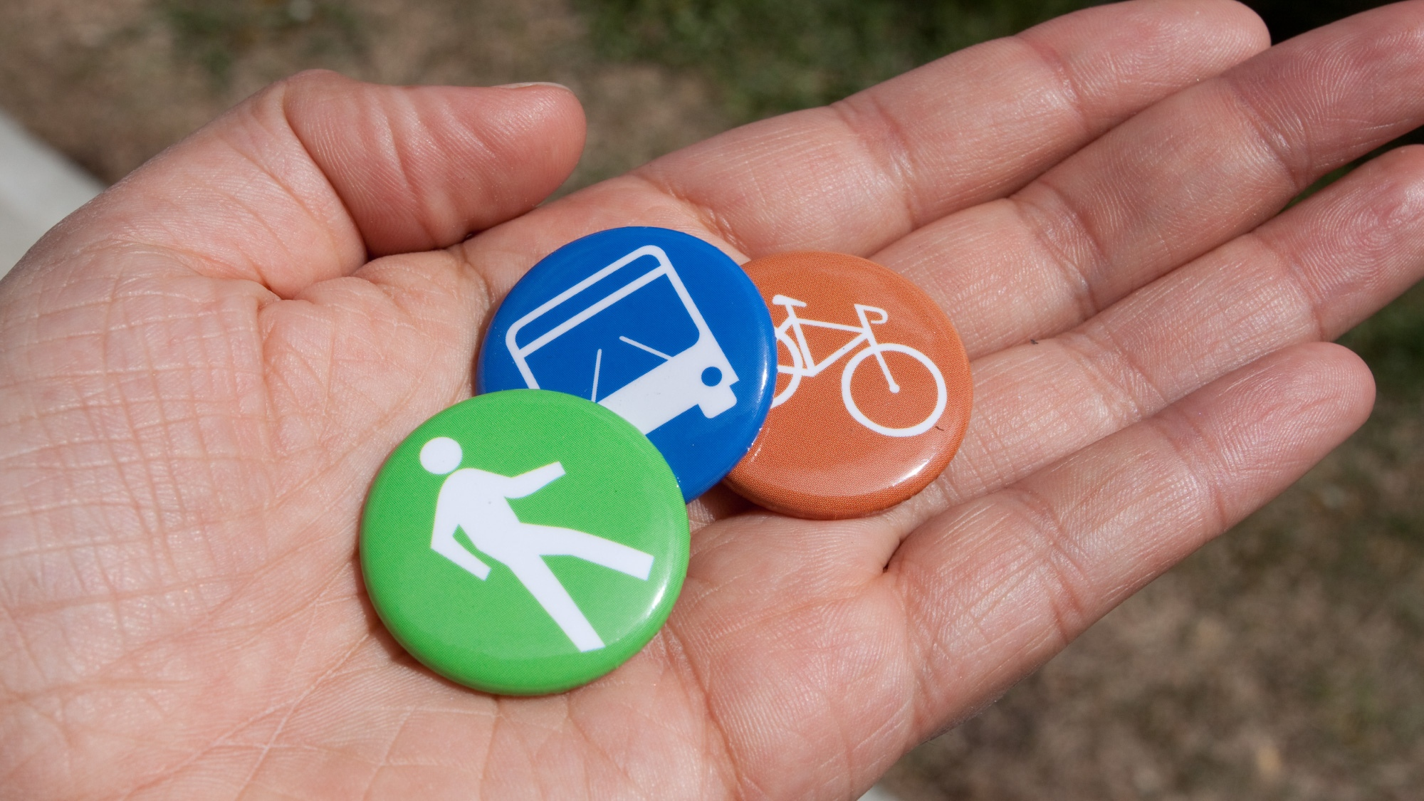 hand holding buttons with icons of different modes of transportation